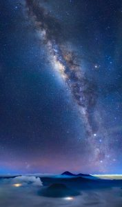 Bromo volcano with milky way the moon and sand strom, East Java island, Indonesia